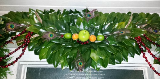 Fresh Magnolia-Leaf Crescent with Christmas Design Accents of Fresh Fruits & Feathers. Individual Cranberries and strung cranberries compliment a center assortment of a large green apple, two green limes and two fresh orange-peel roses. Peacock & pheasant feather accents were added for additional color & flair.