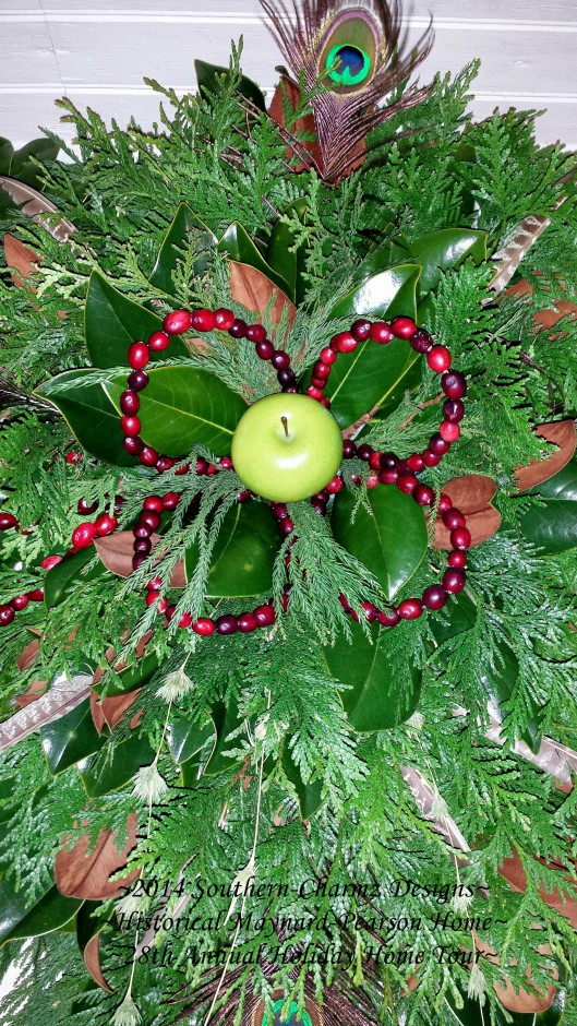 Cranberry flower petals with a large green apple center nestled into gorgeous boughs of cedar and magnolia evergreens to Celebrate Christmas!