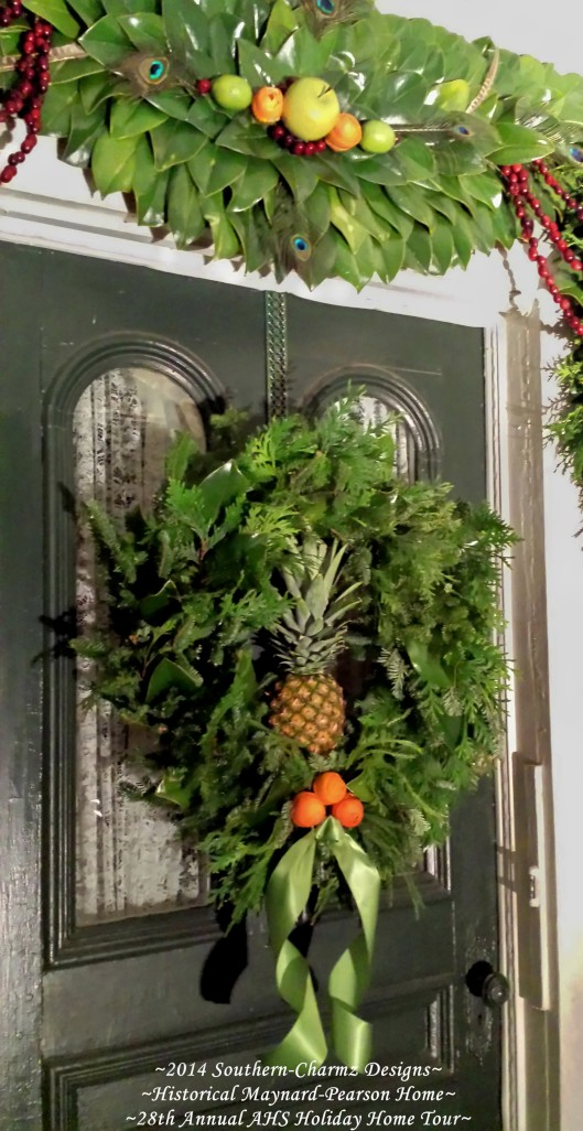 Close-up of the door crescent and Fresh Evergreen wreath. The evergreen wreath consists of fresh frasier fir, fresh magnolia leaves and fresh cedar. A hallmark of Hospitality, a fresh pineapple, sits snugly in the middle and invites everyone to come in. A trio of freshly cut orange peels were fashioned into rosebuds and arranged to represent the Holy Family for Christmas. A silk apple-green ribbon curled in mirror-fashion completes the wreath and is ready to usher everyone into the Holiday Season.